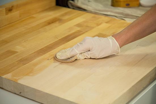 Using Applicator Pad to Apply Sealer to Wood Countertop