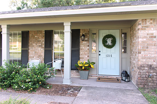 Brick Ranch Home with Blue Front Door White Chairs