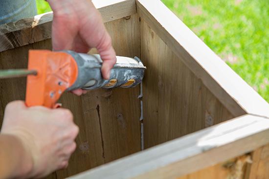 Applying Caulk to Corners of Wooden Planter