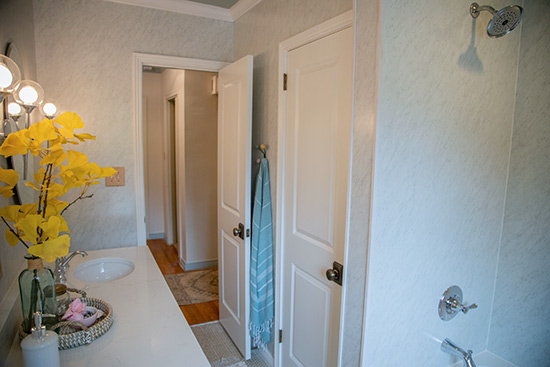Small But Mighty Hall Bathroom with White Trim and Marble Walls
